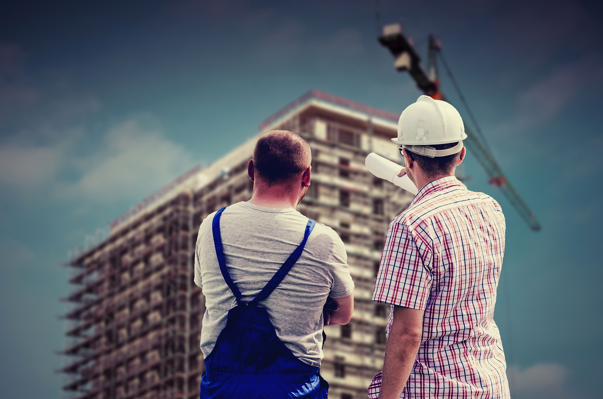 Two men, one in a white hat and the other in overalls, looking at a new apartment building