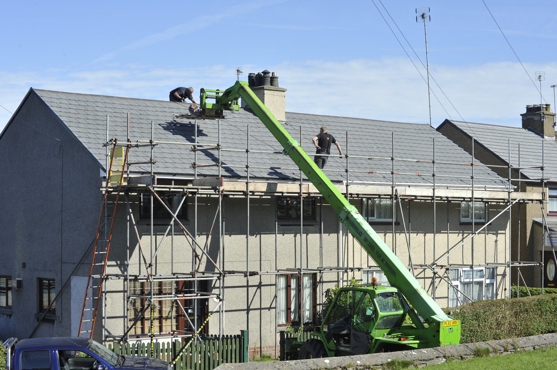 Scaffolder building with crane on a grey house