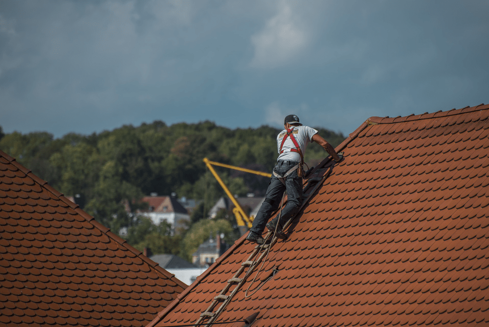Man on a roof fitting new tiles
