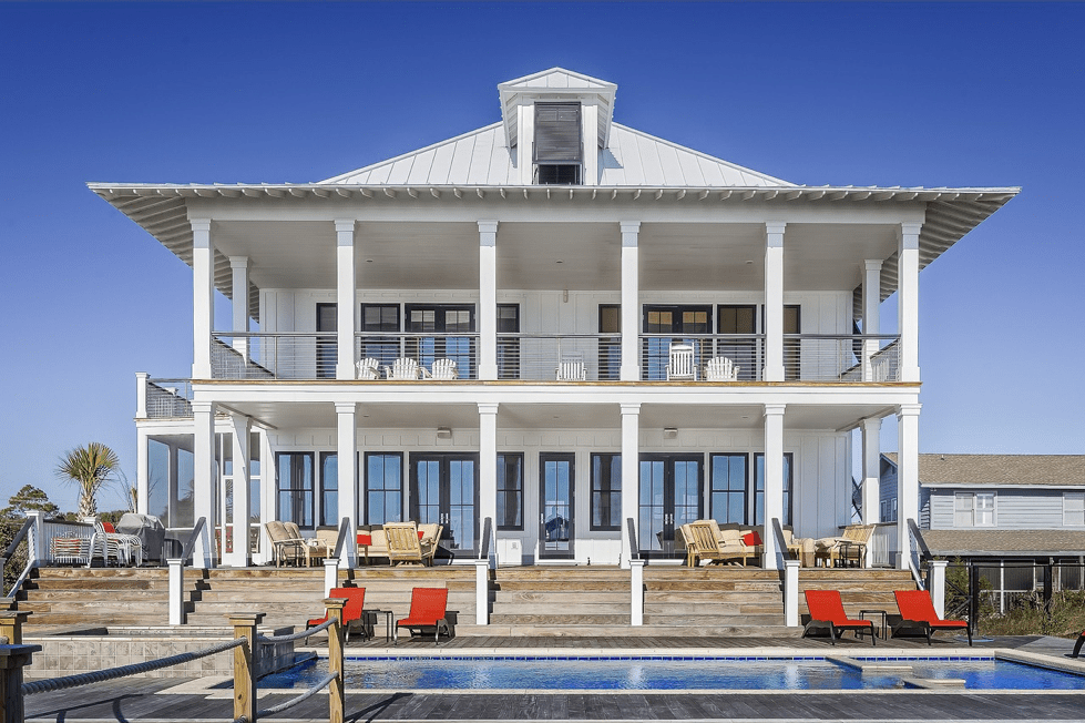 White house with a pool and beach chairs