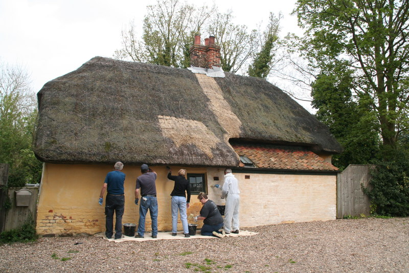 workers repairing lime wash house
