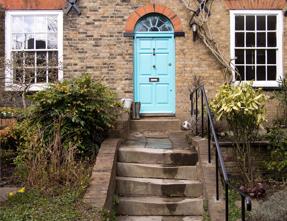 :A brick house with a light blue front door.