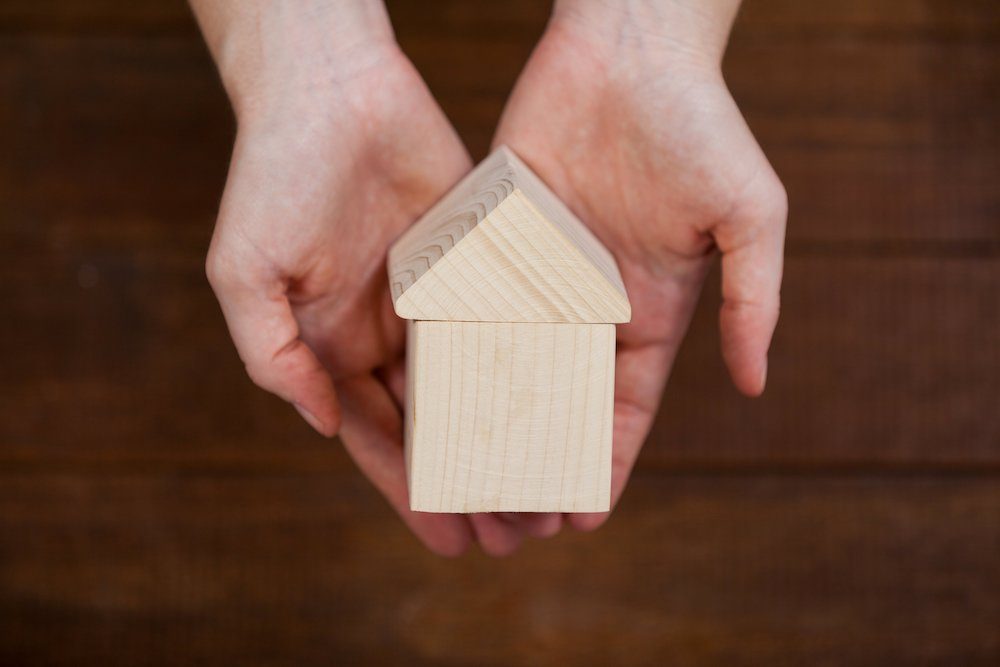 A small wooden house being held in a person's hand