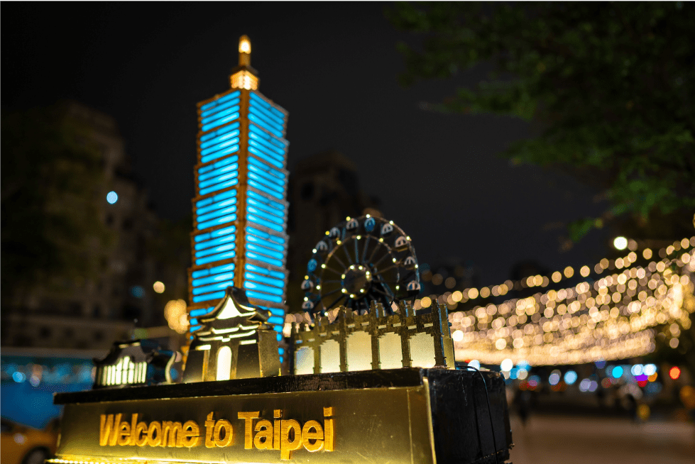 Sign saying 'Welcome to Taipei' in blue neon lights with the Taipei 101 in the background