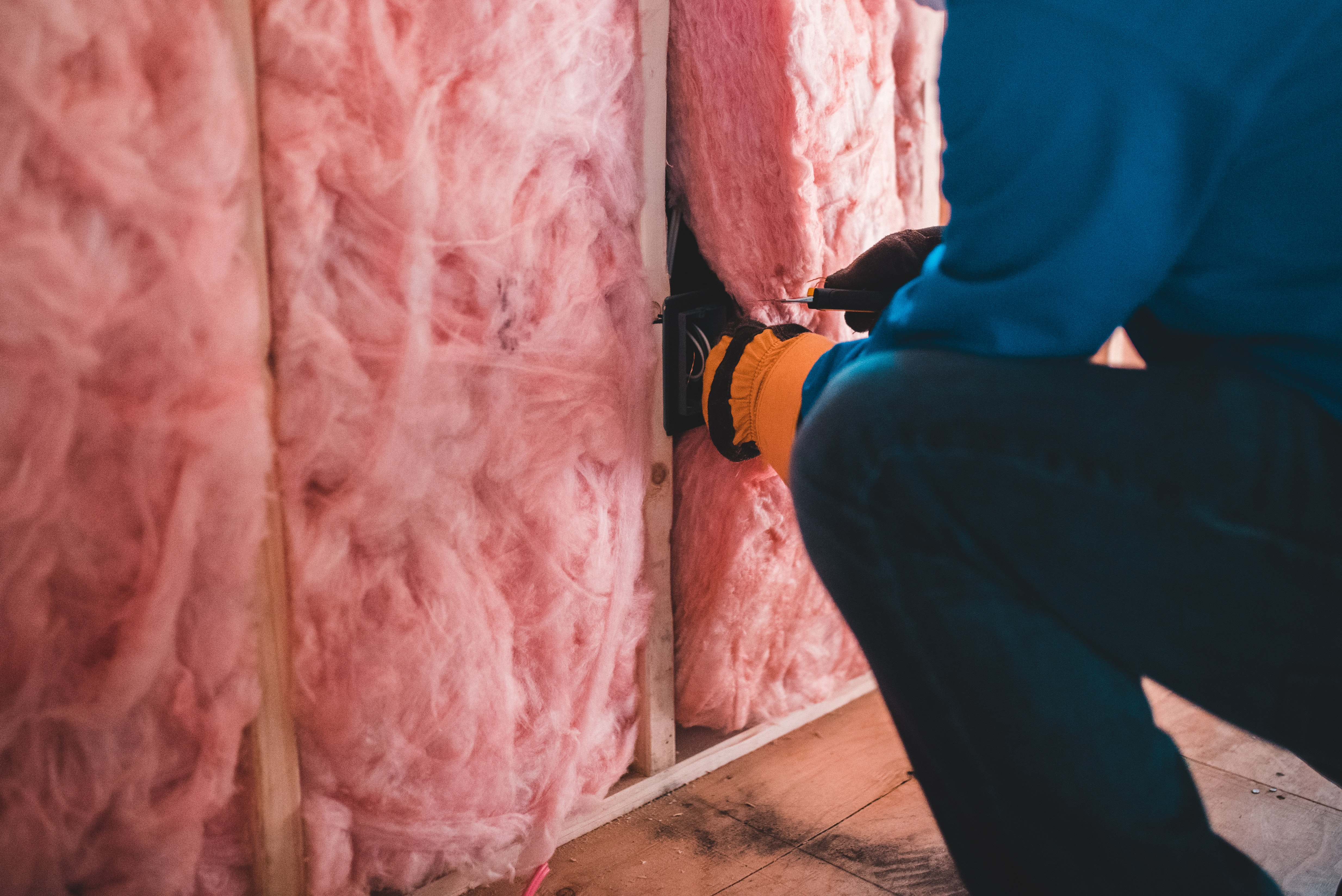 A person installing wall insulation
