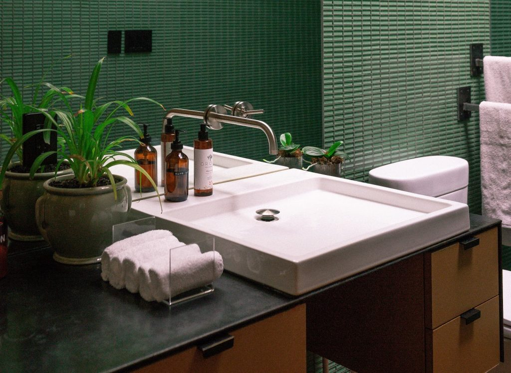 A sink basin in a green tiled bathroom