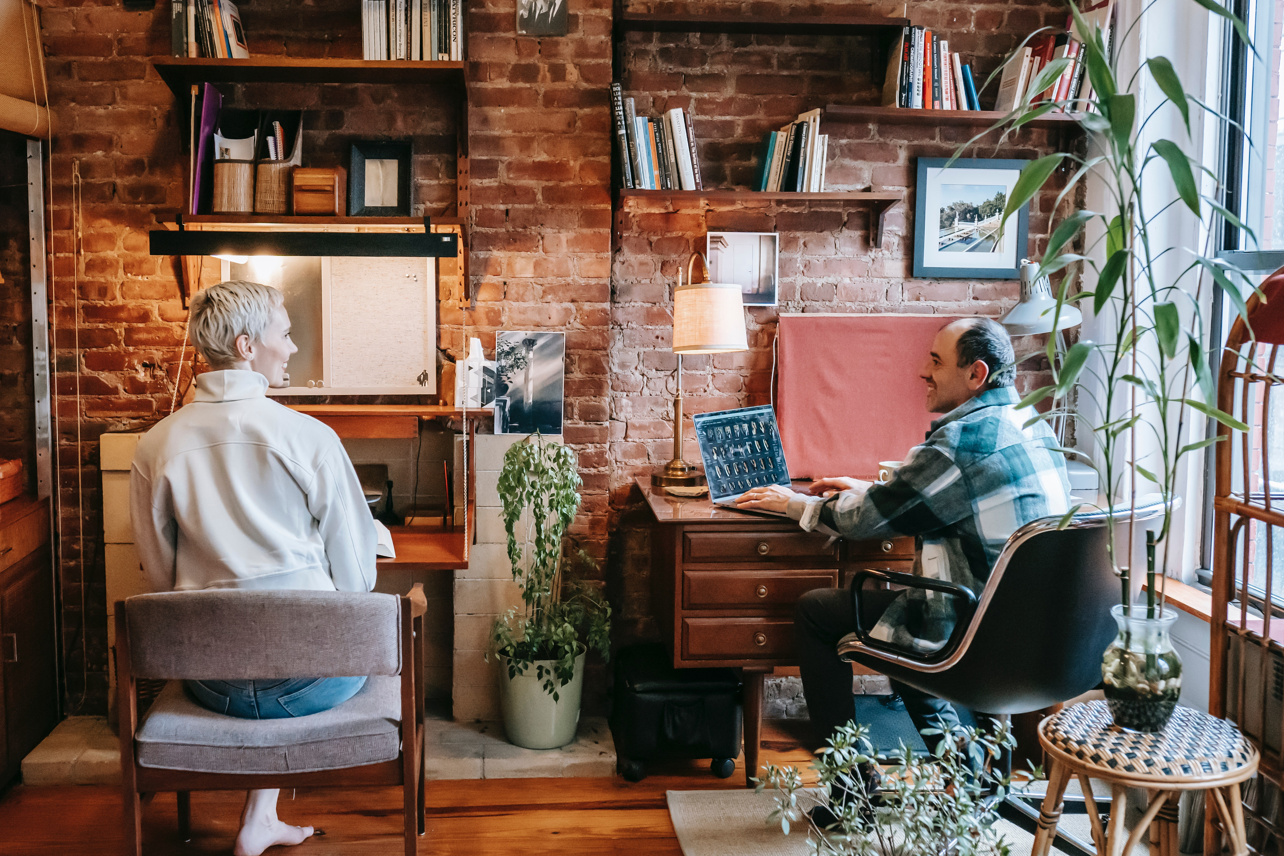 Two people sat at their desks in a home office