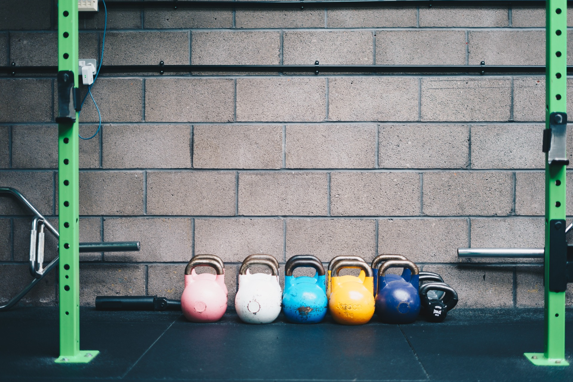 Kettle bells lined up against a concrete basement wall