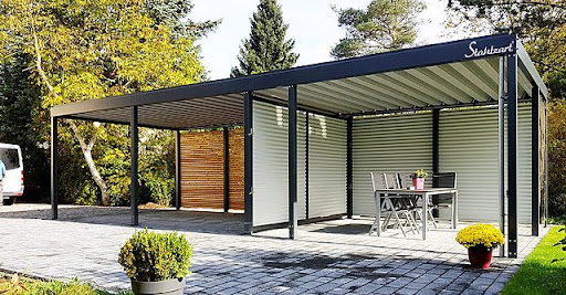A black metal carport with a patio and furniture